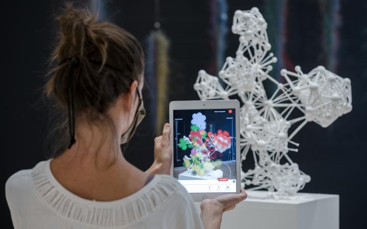 Eine Person steht vor einer weißen 3D-Netzwerk-Skulptur und hält ein Tablet hoch, auf dem mittels Augmented Reality die Skulptur näher untersucht werden kann.