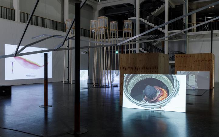 Blick in eine große Halle mit einem Gerüst und weißen Wänden auf denen Videos laufen.