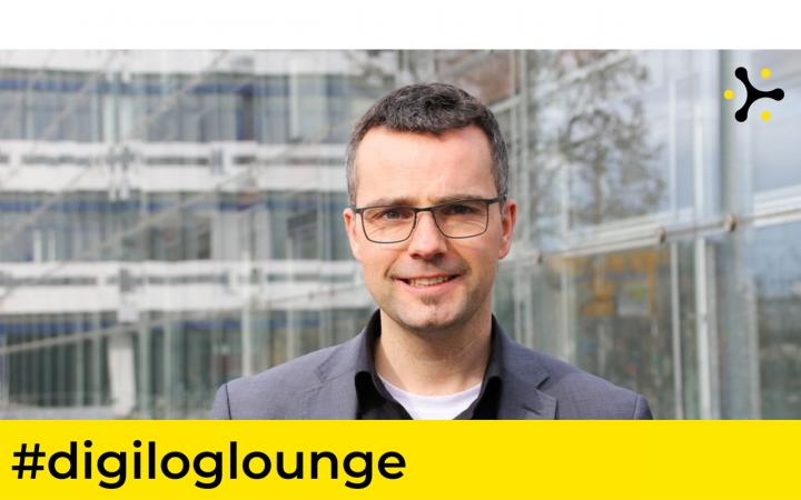 """Portrait of Prof. Dr Marc Debus in front of the Mannheim Centre for European Social Research (MZES). Above the picture is the banner """"#digiloglounge""""."""