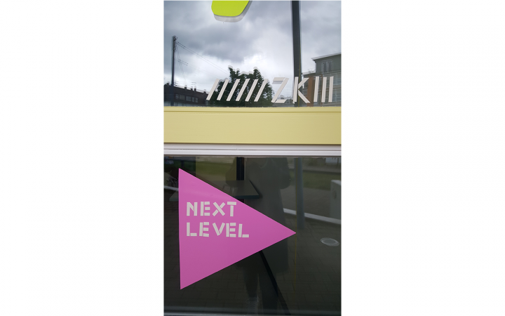 Außenansicht eines Fensters mit Basteleien, dem ZKM-Logo und der Aufschrift »next level«