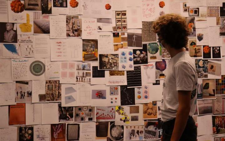 Ein Jugendlicher steht vor einer Wand voller Kunstskizzen.