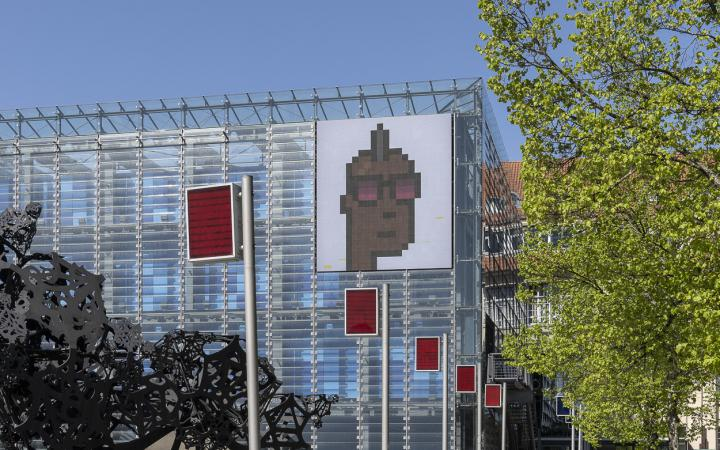 Kryptokunst: Ein illustriertes Gesicht im Pixel-Stil auf der LED Wand des ZKM Kubus.