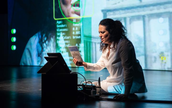 Noa Frenkel is sitting on stage in front of a laptop. Behind her there is a large projection of her, which comes from the laptop's webcam.