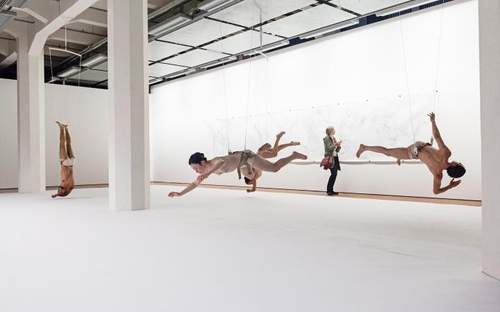 Fünf Tänzer hängen an Drahtseilen kopfüber im Ausstellungsraum.