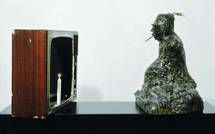 Zu sehen ist auf der linken Seite die Hülle eines alten Röhrenfernsehrs aus Holz wo anstatt des Bildschirmes eine Kerze steht. Gegenüber sitzt eine Buddha Figur mit einem Zahnstocher im Mund.