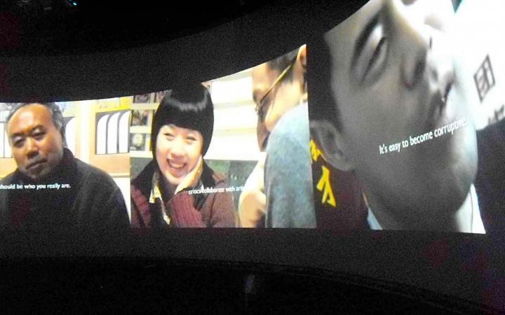 Ein Bildschirm mit drei asiatischen Personen