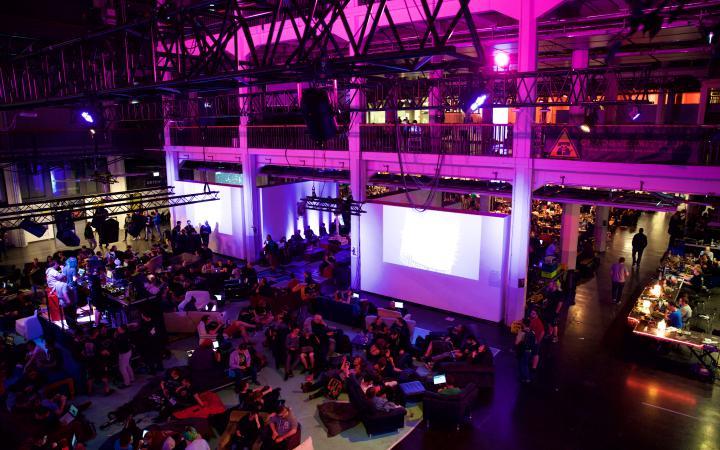 Eine große Halle ist mit Menschen gefüllt und pink beleuchtet