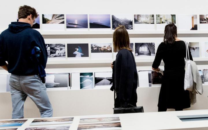 Drei Menschen betrachten Fotografien in einer Ausstellung