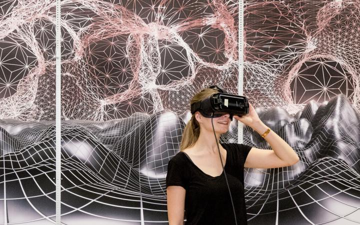 Zwei Frauen mit VR-Brillen stehen vor einer graphischen Landschaft