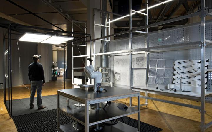 Installation with a robot and milled elements in grey shelves, next to which stands a man with VR glasses