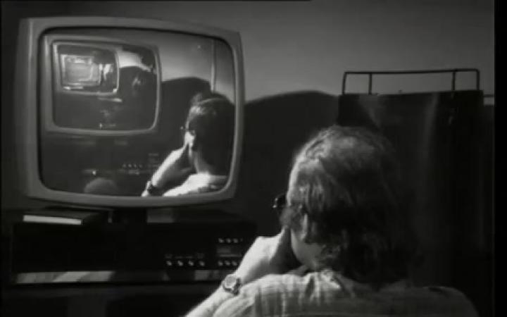 Zu sehen ist ein schwarz/weiß Bild, auf dem EIn älterer Mann sitzt vor einem Röhrenbildschirm auf dessen Bildschirm ein junger Mann zu sehen ist, der auch vor einem alten Fernsehr steht.