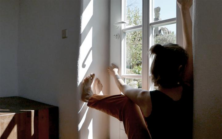 You can see a person sitting on the inside of the windowsill and looking out the window.