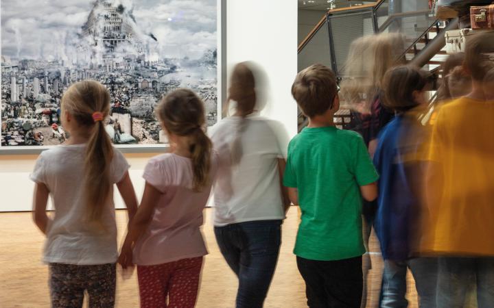 Zu sehen sind eine verschommene Gruppe Kinder vor einem Bild, welches den Turm zu Babel zeigt.
