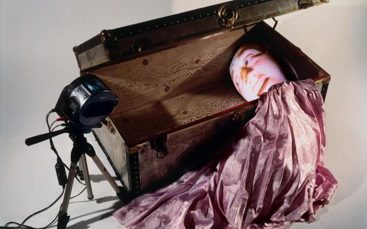 Zu sehen ist eine große Holzkiste in der auf der rechten Seite ein Gesicht, möglicherweise aus Papier, zu sehen. Aus der Kiste kommt ein rosa Stoff heraus.