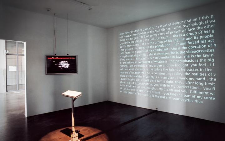 In the middle of a space you can see a keyboard. On one wall hangs a screen, on another wall a text is projected.