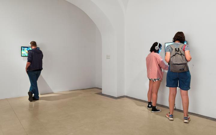 Menschen stehen an Monitoren, die an der Wand befestigt sind und tragen dabei Kopfhörer.