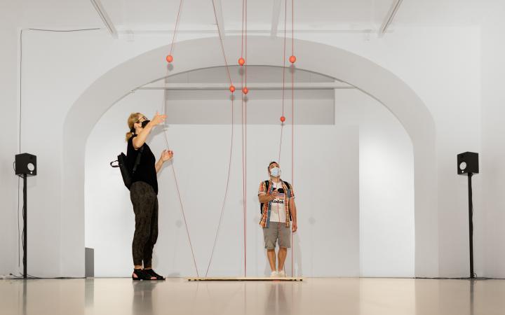 Ein Mann und eine Frau stehen vor einem Kunstwerk, das aus Seilen besteht, welche zwischen der Decke und dem Boden gespannt sind. Die Besucher ziehen die Seile auseinander.
