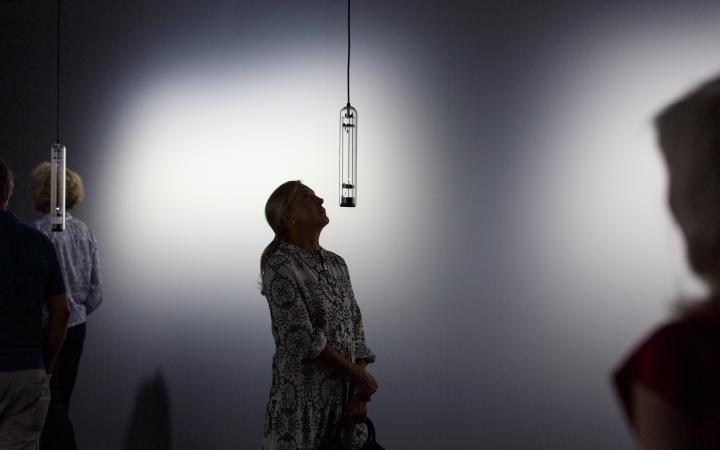 A woman looks up to a sound installation made out of glass.