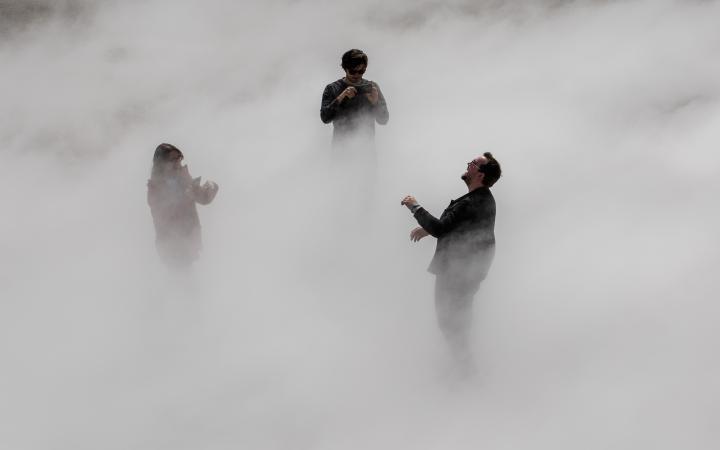 Das Foto zeigt drei lachende Menschen in einem dichten Nebelschleier stehend.