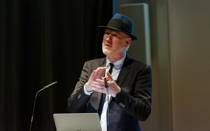 Thomas Paul, media artist and professor in suit and hat, can be seen standing behind a lectern with laptop and gesticulating.