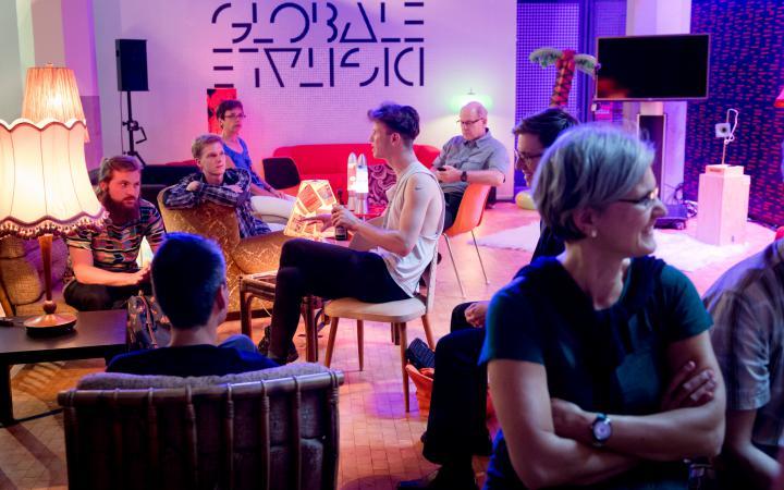Etwa zehn Menschen sitzen in gemütlicher Atmosphäre zusammen und unterhalten sich