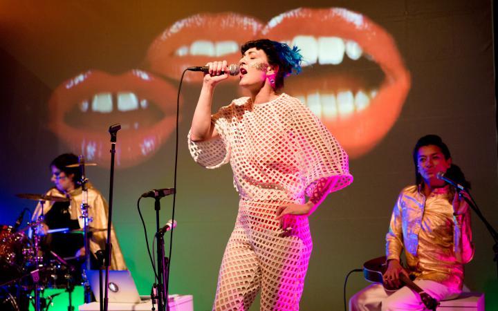 Die Sängerin der Band Chicks on Speed singt leidenschaftlich ins Mikrofon, hinter ihr Schlagzeugerin und Backroundsängerin. Auf einer großen Leinwand im Hintergrund sind drei große Münder zu sehen.