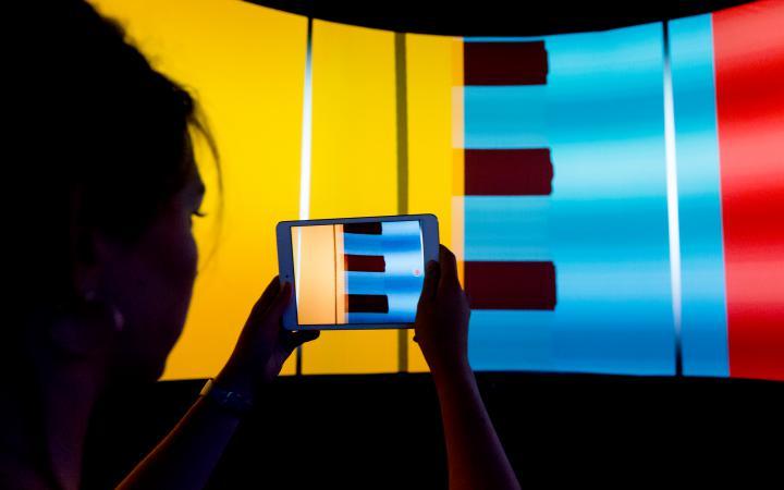 Eine Frau fotographiert mit einem Ipad die bunte Leinwand des Panolabs im ZKM.