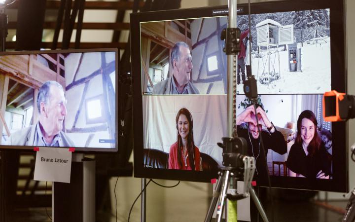 Zwei große Monitore, auf denen per Videoanruf vier Menschen, unteranderen Bruno Latour, zu sehen sind.