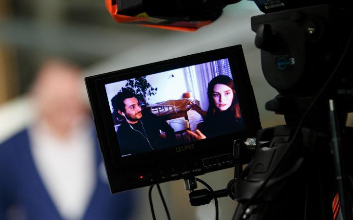 Im Vordergrund ist ein Video-Kamera-Display mit zwei Menschen drauf zu sehen. Hinter dem Display ist Peter Weibel verschwommen zu erkennen.