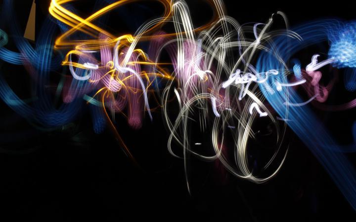 Mit Taschenlampen und einer Kamera mit Langzeitbelichtung wurde ein Licht-Graffiti produziert. In abstrakten Formen wirbeln glebe, weiße und blaue Linien über den schwarzen Hintergrund.