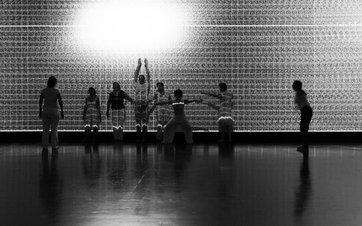 Eine Tanzgruppe führt vor einer Projektionswand Tanzbewegungen aus.