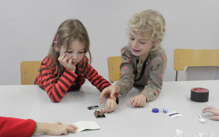 Two girls sitting at a table are building a small robot using a motor, batteries, the head of a toothbrush and other utensils.