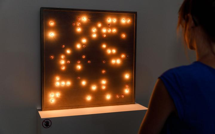 Eine Frausteht vor einem rötlich leuchtenden Kasten mit Lichtpunkten