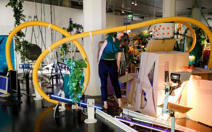 The photo shows an insight into the performance of the opening of »Edge of Now« in the midst of an artinalllation of plants, cardboard and plastic pipes.