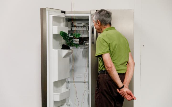 An elderly gentleman stands in front of an open refrigerator, which has been converted into a media installation.