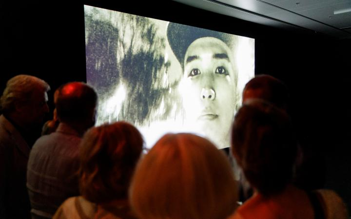 The picture shows a crowd in front of a huge screen showing an Asian young man with Cappy.