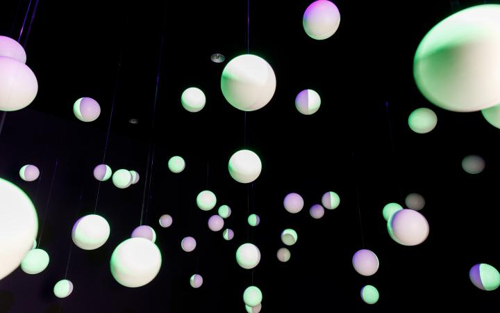 White polystyrene balls hang in a black room, the balls are painted with fluorescent paint and are illuminated.