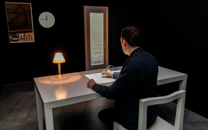 Ein Besucher am Schreibtisch der interaktiven Installation »Beyond Pages« durch Anklicken der Seiten in einem virtuellen Buch, verändert er den Installationsraum.