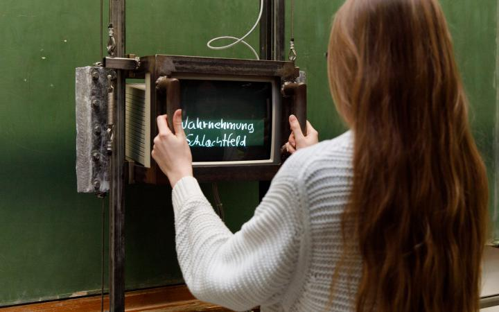 Visitor in front of Fietzek's »blackboard«, an empty green school board on which previously invisible texts appear with the help of a monitor.