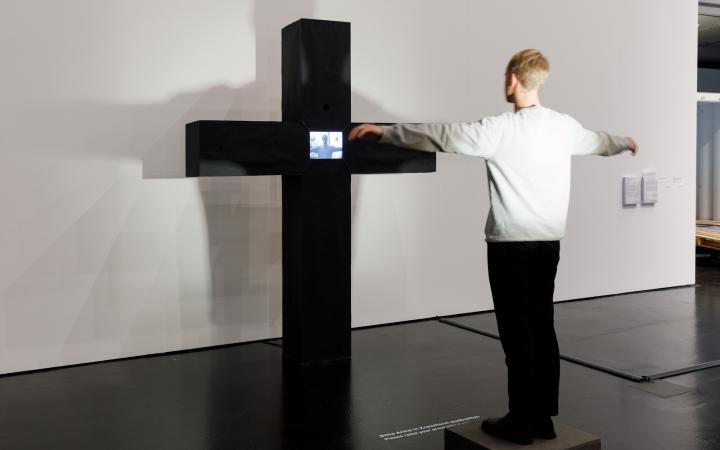 Peter Weibels interaktive Videoskultur: Ein schwarzes massives Kreuz. Dort wo sich die Streben des Kreuzes treffen, ist ein Monitor. Auf dem Monitor zu sehen ist die Person, die vor dem Kreuz steht und ihre Arme ausstreckt, als hinge sie selbst daran.