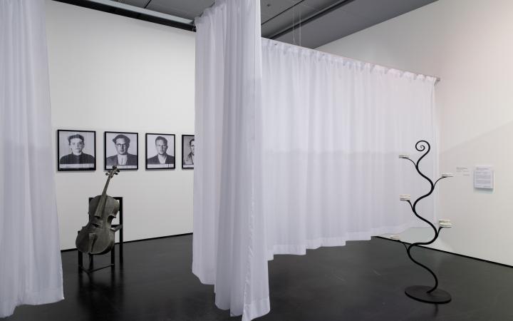 Alles ist schwarz-weiß. Auf der linken Seite an der Wand sind dreieinhalb gerahmte, gehängte Portraits zu sehen. Davor auf einem Stuhl eine Saitenlose Geige. In der Mitte trennt ein weißer Vorhang den Raum. Rechts ein rankenartiges schwarzes Gestell.