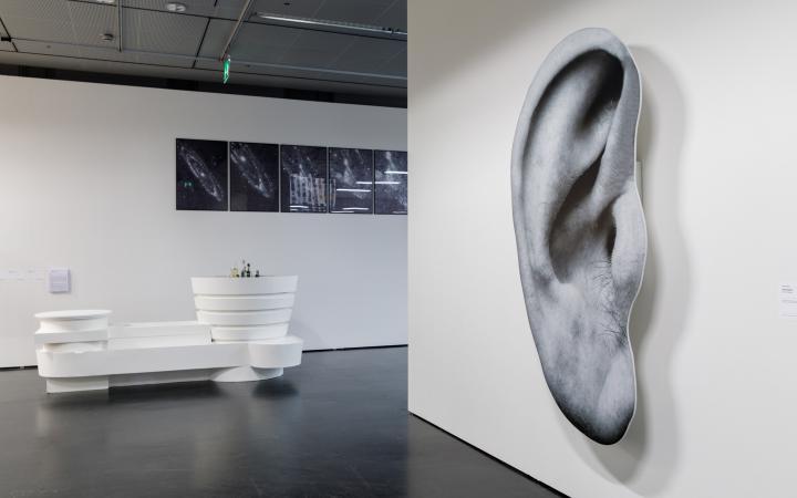 Links eine weiße Installation, die aussieht wie eine futuristische Bar. Im Hintergrund schwarz-weiß Bilder des Universums. Auf der rchten Bildhälfte eine Wand mit einem übergroßen Druck eines Ohres.