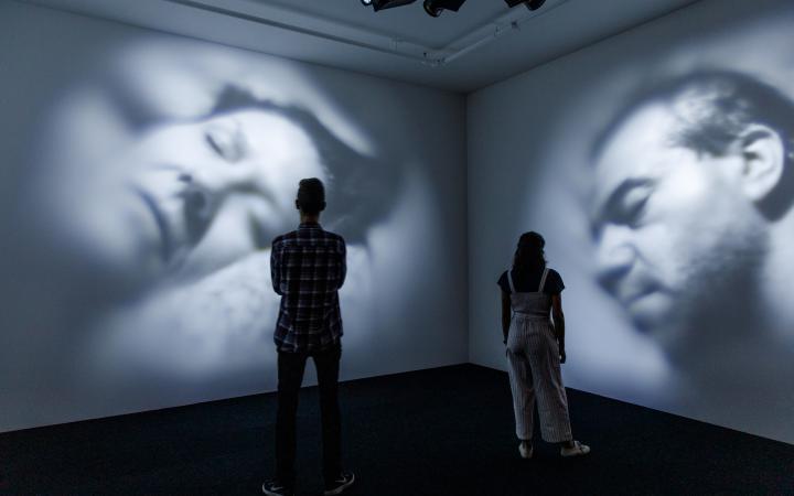 In einem dunklen Raum werden Videos von zwei schlafenden Menschen an die Wand projiziert. Davor stehen zwei BetrachterInnen.