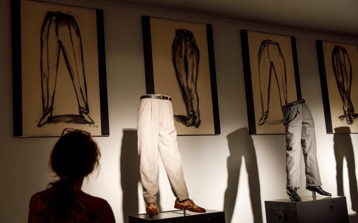 Foto einer Kunstinstallation: zu sehen sind Hosen mit Schuhen auf einer Art Laufsteg, im Hintergrund sind gerahmte Zeichnungen.