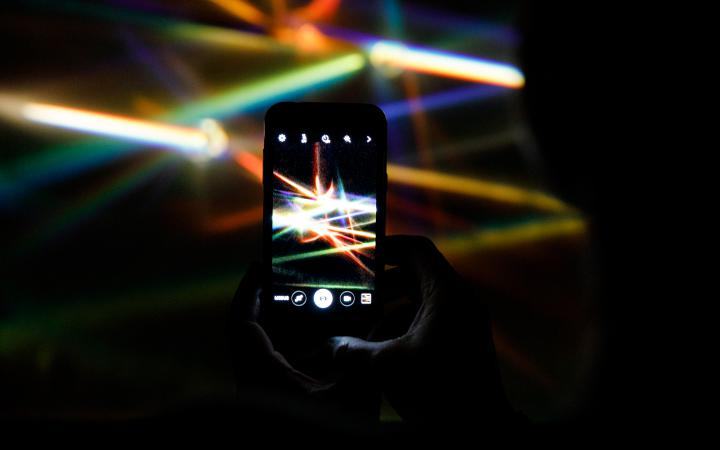 A smartphone in camera mode photographs the beams of colorful light prisms.