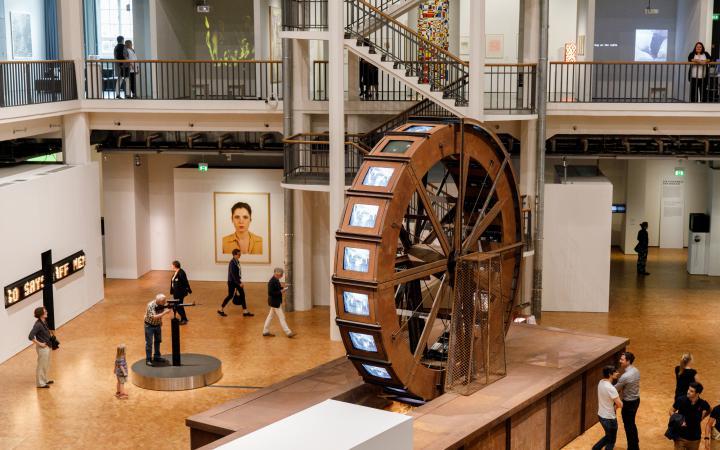 Ein riesiges Mühlrad aus Metall steht in einem Ausstellungsraum. Am Mühlrad befinden sich Röhrenbildschirme worauf Videos von Wasser abgespielt werden.