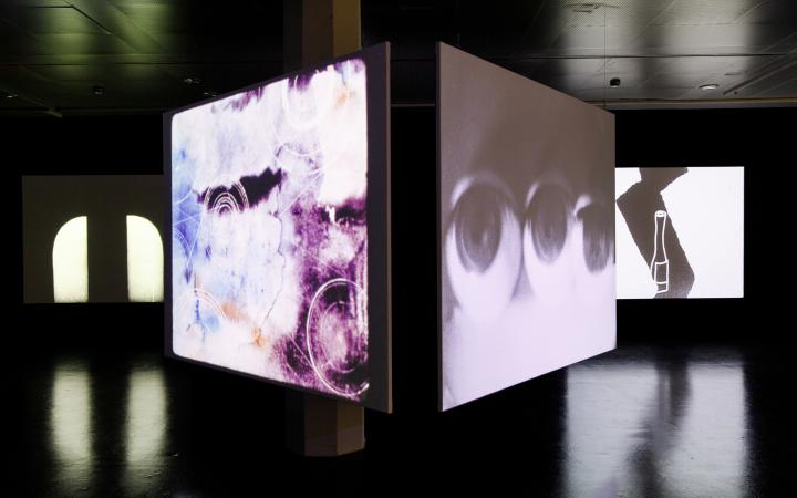 The photo shows two large canvases fixed around a column. On the left canvas there are bright colours to be seen on the right canvas three eyes. IM background a third canvas lights up with a cartoon.