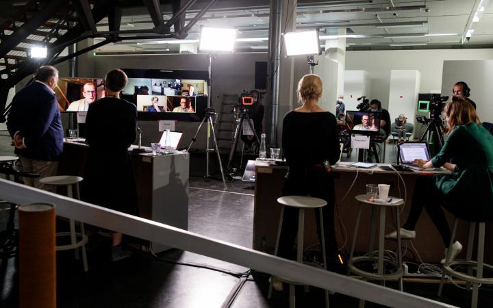 Peter Weibel und drei seiner Kolleginnen stehen an Pulten und werden von Scheinwerfern angeleuchtet, während Kameras auf sie gerichtet sind. Sie schauen auf große Bildschirme, die per Videoübertragung Bruno Latour und andere Streamingfestival TeilnehmerIn