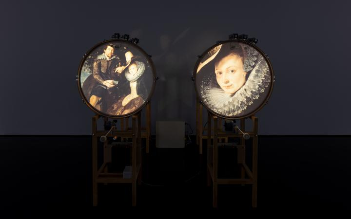You can see two standing drums, each of which shows a picture on the round surface. On the left an ancient married couple and on the right the portrait of a woman.