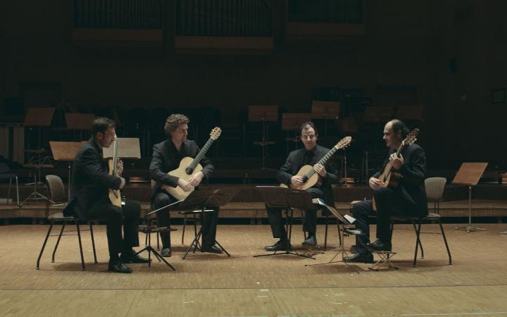 Vier Männer sitzen in einem Halbkreis mit Gitarren in ihren Händen.